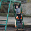 Young boy climbing on monkey bars — Stock Photo