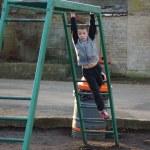 Young boy climbing on monkey bars — Stock Photo #43169735