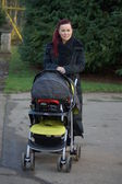 Young mother with child in pushchair — Stock Photo