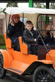 Young family on an orange car fairgound ride — Foto de Stock