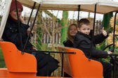 Young family on an orange car fairgound ride — Stock Photo