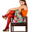 Girl in red tights sits in old wooden chair — Photo #16972071