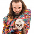 The bearded man in the colour shirt with a skull in his hands - Stock Photo