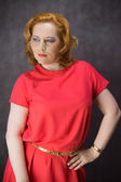 Red-haired woman dressed in a red dress — Stock Photo