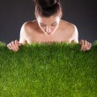 Woman and green grass against a dark background. — Stock Photo