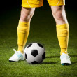 Soccer ball and a feet of a soccer player - Stock Photo