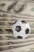 Soccer ball on background of dollars — Stock Photo