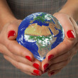 Women's hands holding the earth. — Stock Photo