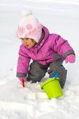 маленькая девочка, играя со снегом — Стоковое фото