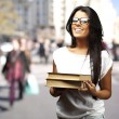 Portrait of young girl holding books at crowded city — Stock Photo