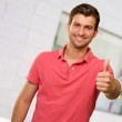 Young man smiling with thumbs up — Stock Photo #12665010