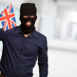 Portrait of a man wearing mask holding a flag — Stock Photo #12666438