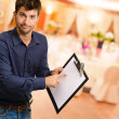 Young Man Holding Clipboard - Stockfoto