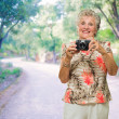 Happy Senior Woman Standing With Camera — Stock Photo #12666877