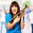 Surprised woman holding trumpet - Stock Photo