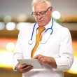 Stock Photo: Portrait Of Male Doctor Holding Tab