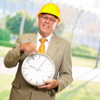Portrait Of A Senior Man Holding A Wall Watch - Stock Photo