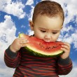 Kid tasting a watermelon slice against a sky background — Stock Photo