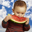 Stock Photo: Kid tasting a watermelon slice against a sky background