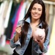 Portrait Of A Female Holding A Coin And Piggybank - Stock Photo