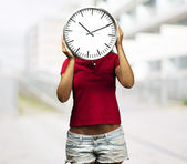 Woman holding clock in front of her head — Stock Photo
