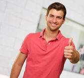 Young man smiling with thumbs up — Stock Photo