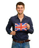 A Young Man Holding A Flag Of United Kingdom — Stock Photo