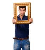 Un joven sosteniendo y mirando a través del marco — Foto de Stock