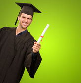 Young Man In Graduation Gown Holding Certificate — Stock Photo