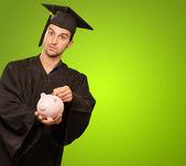 Mladý muž v maturitní šaty drží prasátko — Stock fotografie