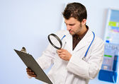 Doctor With Magnifying Glass And Clipboard — Stock Photo