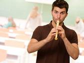 Porträtt av en ung man som spelar flöjt — Stockfoto