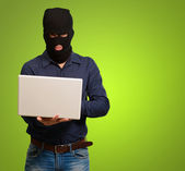 Young male thief holding laptop — Stock Photo