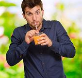 Junger mann trinken saft — Stockfoto