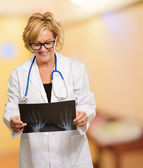 Female Doctor Looking At X-ray Report — Stock Photo