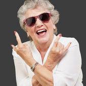 Senior woman wearing sunglasses doing funky action — Stockfoto