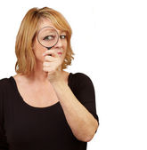 Woman using a magnifying glass — Foto Stock