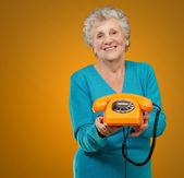 Mujer madura feliz celebración de teléfono — Foto de Stock