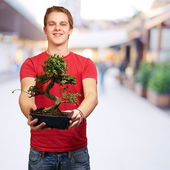Portrait of a young man holding a pot — Stock Photo