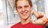 Portrait of a young man holding a stopwatch — Stok fotoğraf