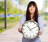 A Young Girl Holding A Clock And Making Face — Stock Photo
