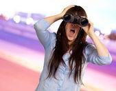 Retrato de uma jovem mulher olhando através de binóculos — Foto Stock