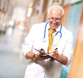 Happy Male Doctor Writing On Clipboard — Stockfoto