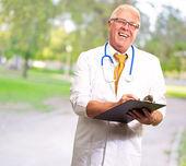 Feliz médico masculino escrevendo na área de transferência — Fotografia Stock