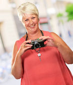 Senior Woman Holding Camera — Stock Photo