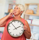 Senior Woman Holding A Clock And Thinking — Stockfoto