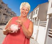 Senior frau hält ein sparschwein — Stockfoto