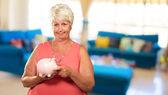 Frau setzen Münze im Sparschwein — Stockfoto