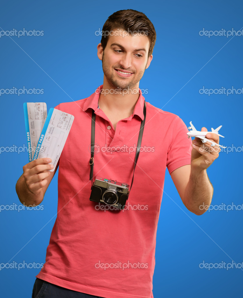 Man Holding Boarding Pass And Airplane On Blue Background  Stock Photo #12665067