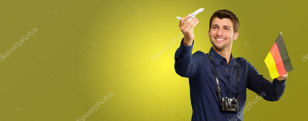 Man Holding A Miniature Airplane And German Flag On Coloured Background — Lizenzfreies Foto #12665158